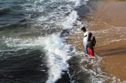 una chica musulmana con su compañero en refrescándose en el mar