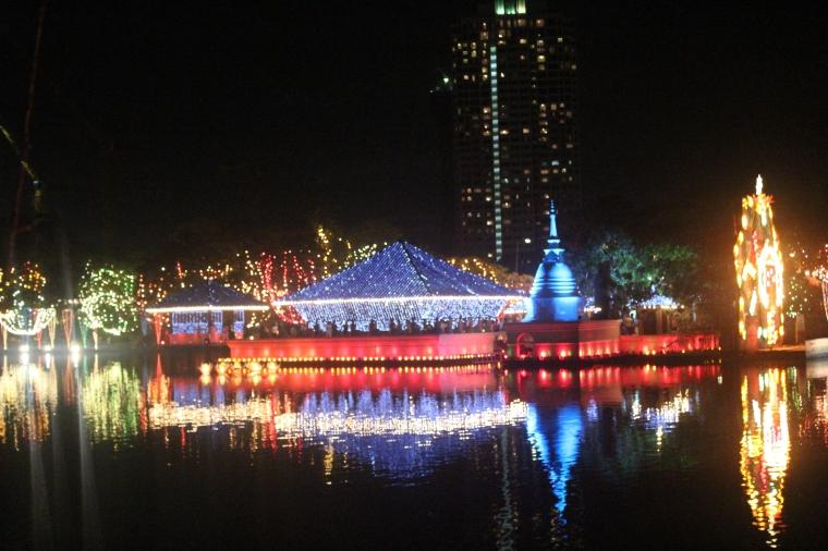 Se puede ver la Estupa budista iluminada de azul y otro Pandal del lado derecho